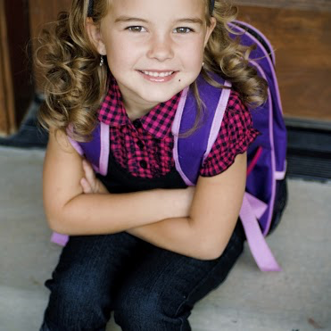 A young girl wearing a backpack is ready to start school.