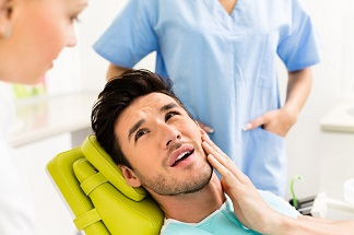 Man With Hand On Mouth In Dentist Chair, Mouth Open and Looks To Be In Pain